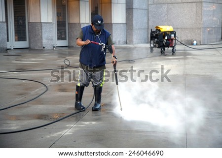 BRONX, NEW YORK - MAY 29: Man uses pressure washer to clean Yankee Stadium sidewalk.   Taken May 29, 2014 in the County of the Bronx, NY.