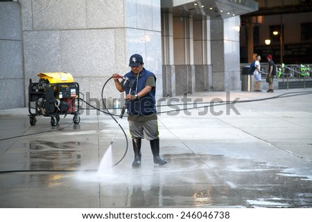 BRONX, NEW YORK - MAY 29: Man uses pressure washer to clean Yankee Stadium sidewalk.   Taken May 29, 2014 in the County of the Bronx, NY. - stock photo