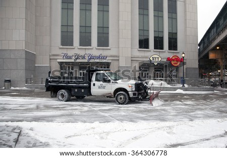 BRONX, NEW YORK, USA - FEBRUARY 19: A truck with a plow clears snow in front of Yankee Stadium.  Taken February 19, 2015 in the Bronx,  New York. - stock photo