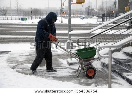 BRONX, NEW YORK, USA - FEBRUARY 19: Man uses salt spreader during snowfall.  Taken February 19, 2015 in the Bronx,  New York. - stock photo