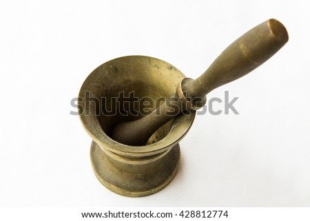 Bronze ancient mortar to grind coffee on white table. Elegant classic coffee beans. Heavy metal coffee mortar.