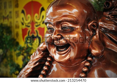 Bronze Coloured Budai Statue at a Taoist Shrine - Budai is Commonly Known as the Laughing Buddha - stock photo