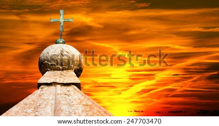 Bronze cross above a marble roof at beautiful sunset with cloudy sky - stock photo
