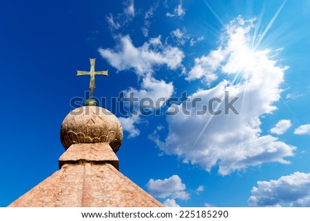 Bronze Cross on Blue Sky / Bronze cross above a marble roof on a blue sky with clouds and sun rays - stock photo