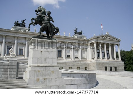 Bronze horse tamer in front of Austrian Parliament Building - Vienna, Austria - stock photo
