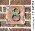 Bronze house number eight on a weathered plate - stock photo
