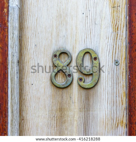 bronze house number eighty nine on a wooden plank - stock photo