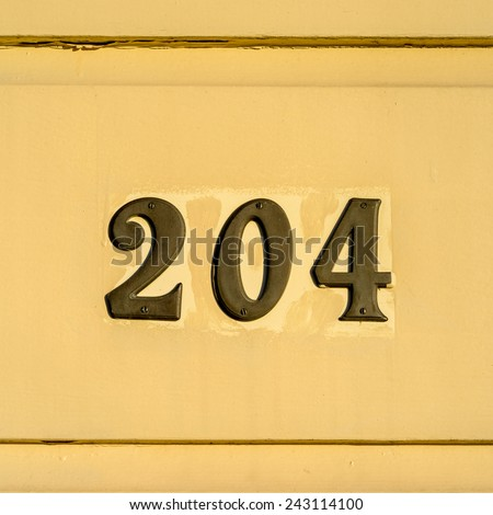 bronze house number two hundred and four. - stock photo