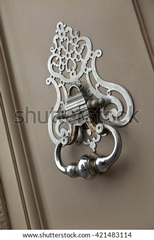 Bronze knocker on the door of a French mansion - stock photo