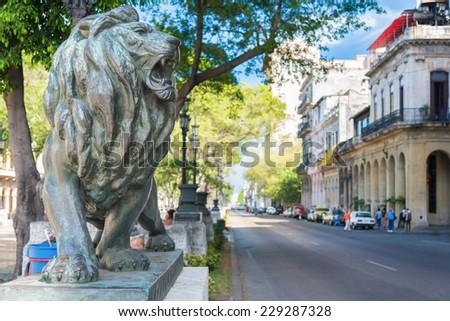 Bronze lion and historic buildings at El Prado Boulevard, a famous landmark in Havana - stock photo