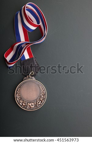 bronze medal with ribbon on the blackboard