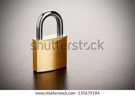 Bronze padlock on table closeup - stock photo