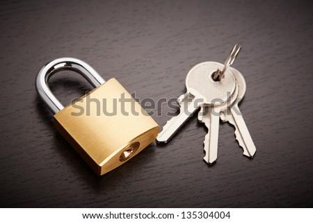 Bronze padlock with keys on table - stock photo