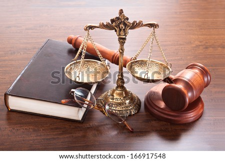 Bronze scales, gavel, glasses, a book on the table - stock photo