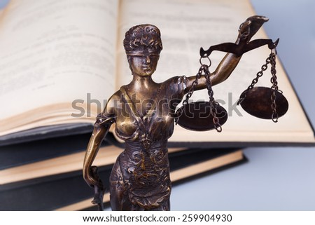 Bronze statue of justice with lawyer books - stock photo