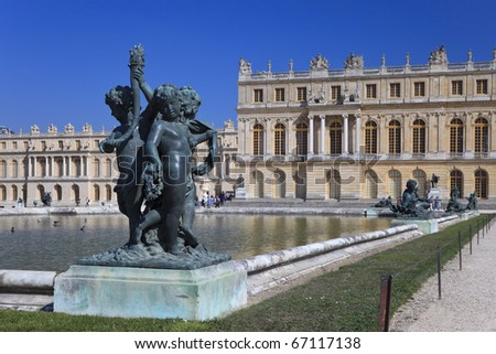 Bronze statue on the background royal palace in Versailles, France