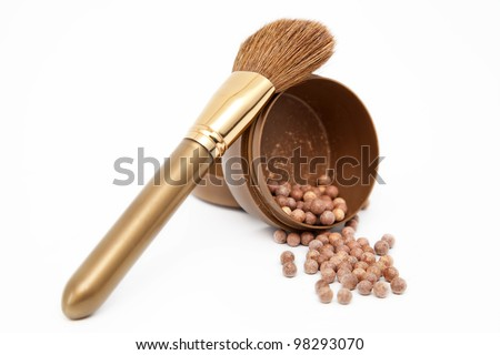 Bronzing pearls and makeup brush isolated on white