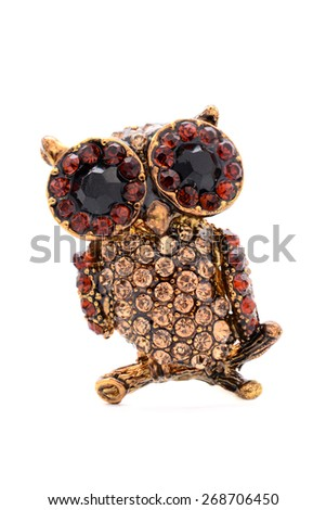 brooch in the form of an owl on a white background - stock photo