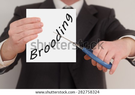 Brooding, man in suit cutting text on paper with scissors