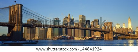 Brooklyn Bridge and East River at sunrise with New York City, NY skyline