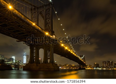 Brooklyn bridge and Freedom Tower peeking under Manhattan bridge arch at night.