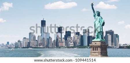 Brooklyn Bridge and Manhattan Skyline with the Statue of Liberty in foreground, New York City. - stock photo