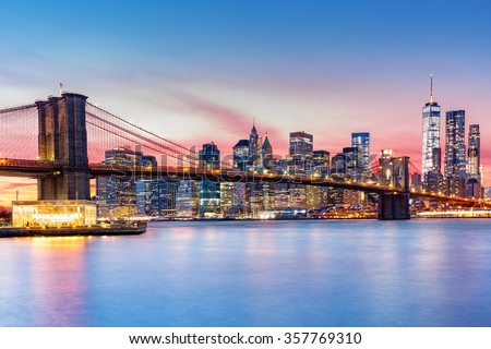 Brooklyn Bridge and the Lower Manhattan skyline under a purple sunset - stock photo