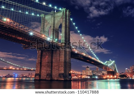 Brooklyn Bridge closeup over East River at night in New York City Manhattan with lights and reflections. - stock photo