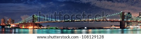 Brooklyn Bridge panorama over East River at night in New York City Manhattan with lights and reflections. - stock photo