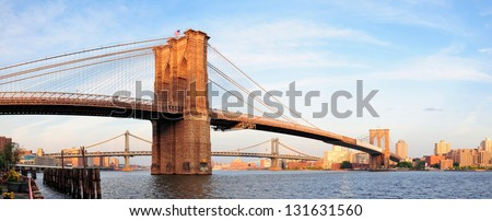 Brooklyn Bridge panorama view over East River viewed from New York City Lower Manhattan waterfront at sunset. - stock photo