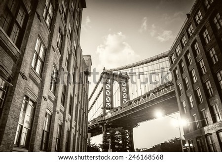 Brooklyn Bridge seen among city buildings at night. - stock photo