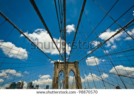 Brooklyn Bridge suspension cables wide angle with blue sky white clouds - stock photo