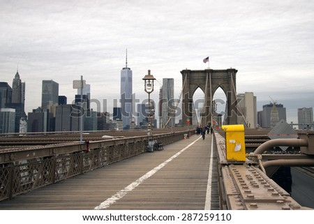 Brooklyn Bridge  walkway in New York City with pedestrians in the distance on an overcast day - stock photo