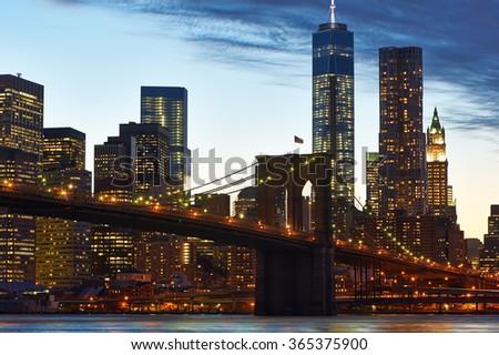 Brooklyn Bridge with lower Manhattan skyline in New York City at evening - stock photo
