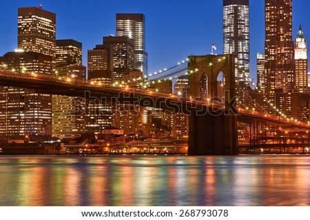 Brooklyn Bridge with lower Manhattan skyline in New York City at night - stock photo