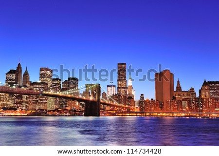 Brooklyn bridge with New York City Manhattan downtown skyline at dusk illuminated over East River with blue clear sky. - stock photo