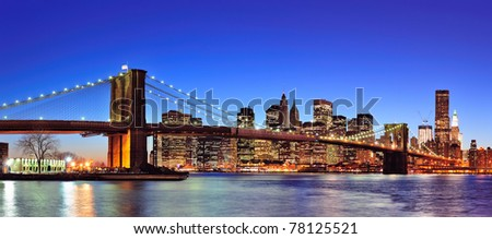 Brooklyn bridge with New York City Manhattan downtown skyline panorama at dusk illuminated over East River with blue clear sky. - stock photo