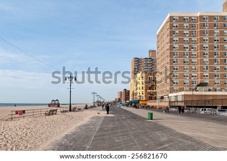 BROOKLYN, NEW YORK, USA - NOVEMBER 14: People sitting on benches in the sun and walk in front of an apartment building on the boardwalk at Brighton Beach, Brooklyn NY at November 14, 2011.  - stock photo