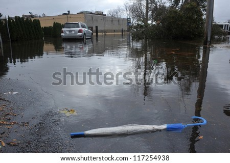 BROOKLYN, NY - OCTOBER 30: A dropped umbrella on the ground in the Sheapsheadbay neighborhood due to flooding from Hurricane Sandy in Brooklyn, New York, U.S., on Tuesday, October 30, 2012. - stock photo