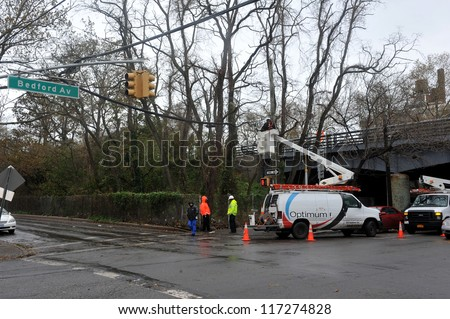 BROOKLYN, NY - OCTOBER 30: A utility company works on overhead wires while the electricity is off  in the Sheapsheadbay neighborhood due to flooding from Hurricane Sandy in Brooklyn, New York, U.S., on Tuesday, October 30, 2012. - stock photo