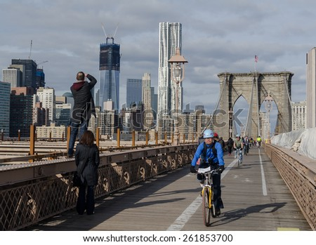 Brooklyn, NY, USA - January 8, 2012 - Bicycle Riders and Tourists enjoying a warm winter day on the Brooklyn Bridge. Freedom Tower and New York by Gehry Buildings in the background. - stock photo