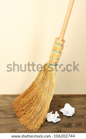 Broom and papers on floor in room - stock photo