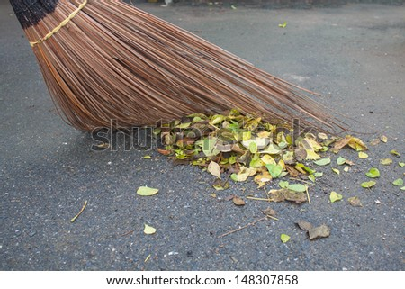 Broom, dry leaves, cleaning leaves on floor - stock photo