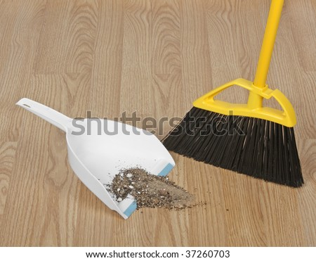 Broom Sweeping Up Dirt Into Dust Pan On Hardwood Floor