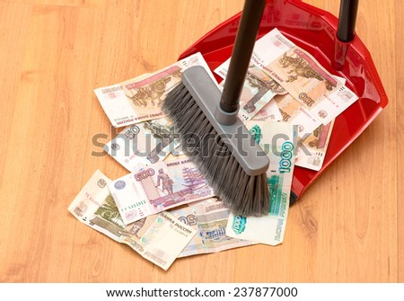 Broom sweeps the Russian ruble in the garbage scoop - stock photo