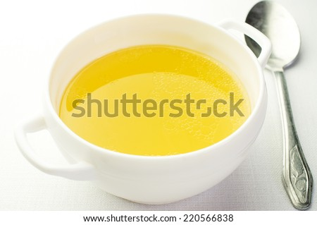 Broth, bouillon in a ceramic bowl. Next vintage spoon - stock photo