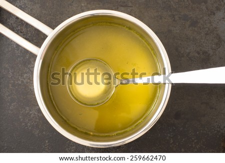 Broth in a steel pot on the stove - stock photo