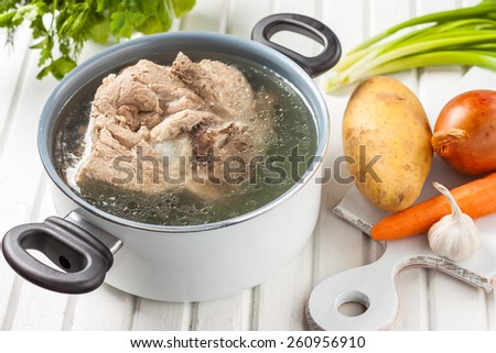 broth in a white pot. vegetable ingredients for a soup - stock photo