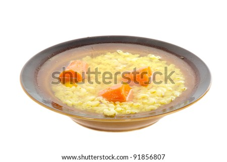 Broth soup with pasta and carrots on a white background.