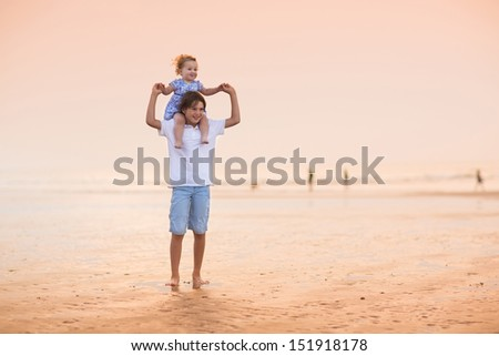 Brother and baby sister playing on a beautiful beach at sunset